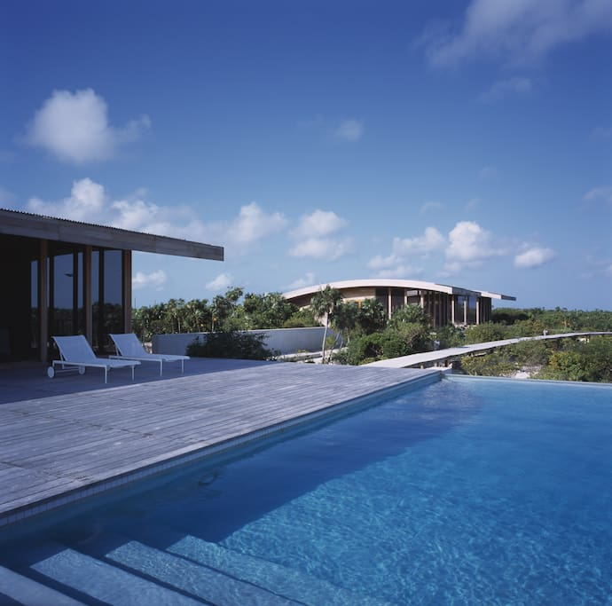 The main deck in front of the living room with the fresh water pool and a bedroom building beyond.