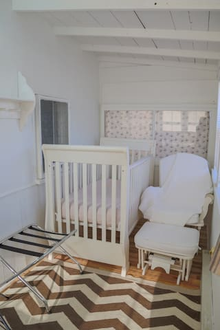 A view of the crib and rocker.