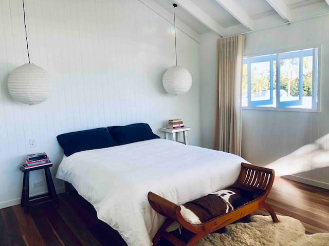 The master bedroom is on a mezzanine floor and looks north west to Wollumbin (Mt Warning) and north east into the graceful branches of Byron's oldest fig tree.
