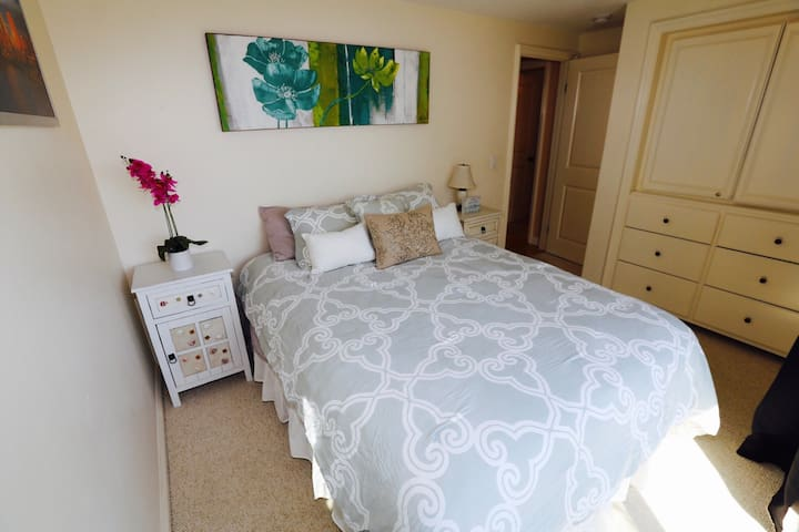Guest bedroom with queen bed, flat screen TV and balcony