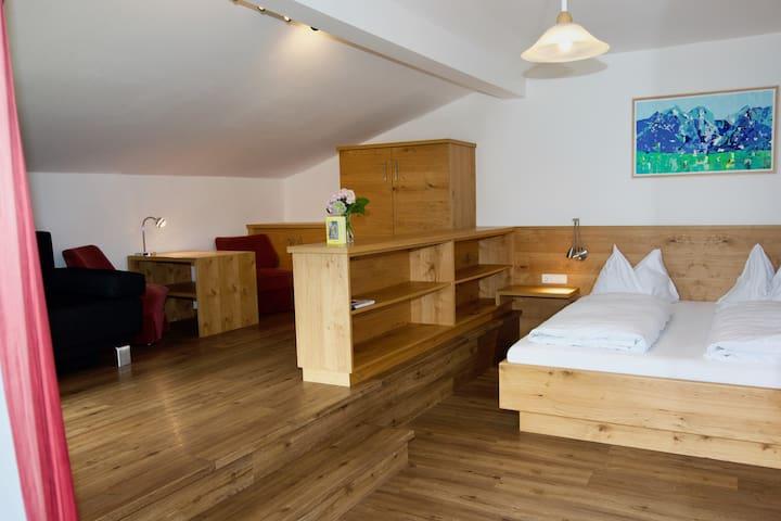 Schlafzimmer mit zusätzlichem Sofa und kleiner Sitzgelegenheit um perfekt die Energiespeicher wieder aufzuladen.
