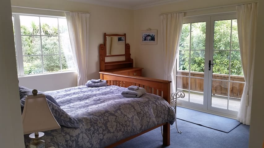 The bedroom - catches the afternoon sun, French doors opening onto a sun drenched deck