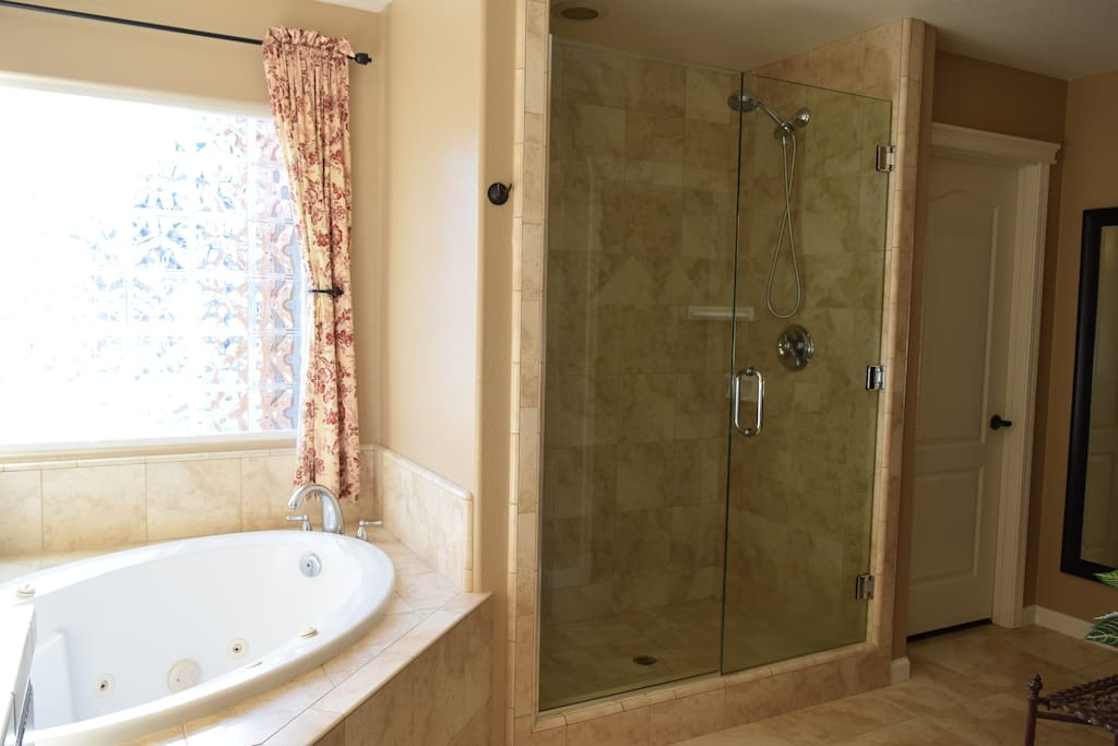 Enjoy the large glass door tile shower and jacuzzi tub