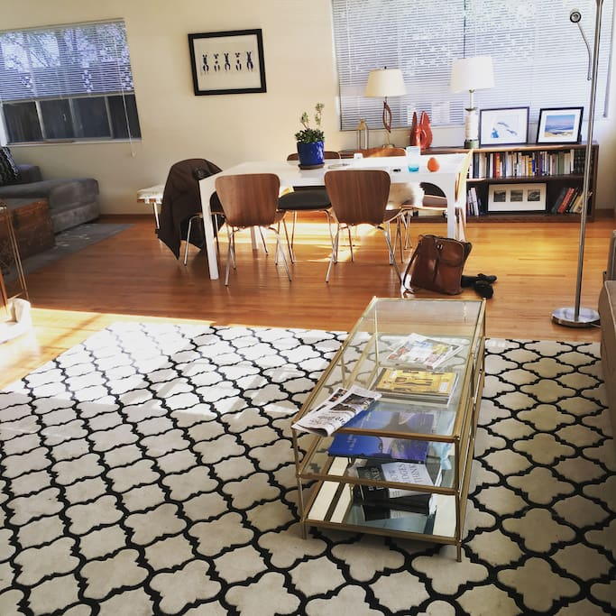 Full living space, with two couch areas, a TV and a dining room table