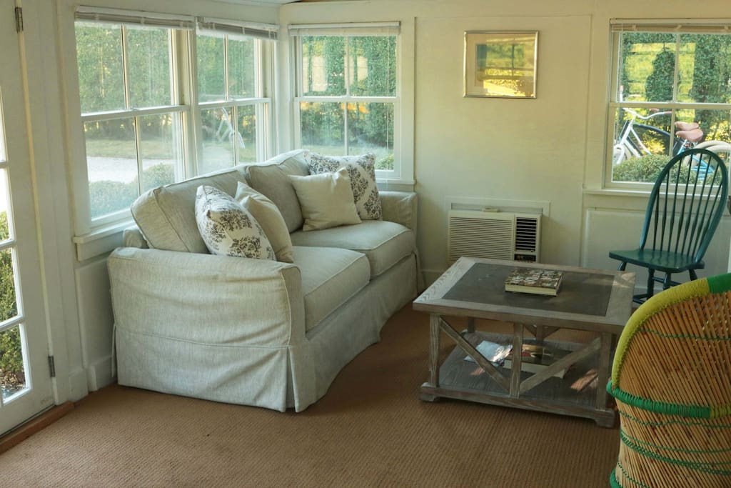Cozy front porch with couch, tv, sonos and coffee table. Screens on window.