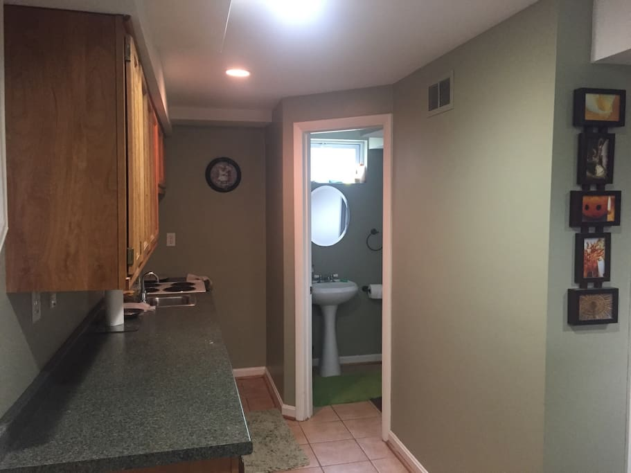 Kitchen, electric stove, coffee maker, toaster, fridge, bathroom entrance