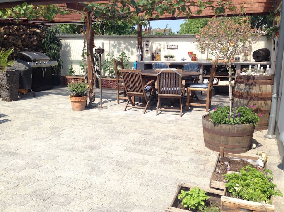 Outdoor dining area - room enough for 2 tables. 2 Barberque posibilities. At summer grapes are hanging from the roof :-)
