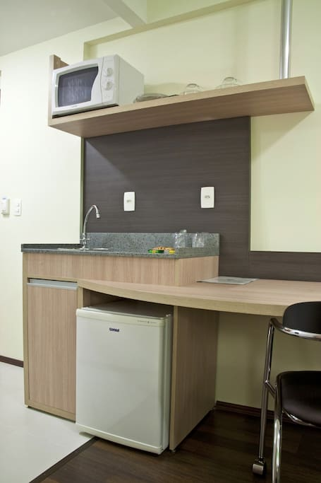 Cozinha compacta com microondas, frigobar, pia, copos, talheres e pratos.