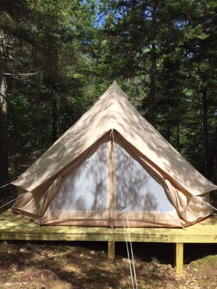 Walk through the scenic woods behind our historic farm house to find our beautiful 13' canvas bell tent. It's set up on a wooden platform to keep you dry and comfortable.