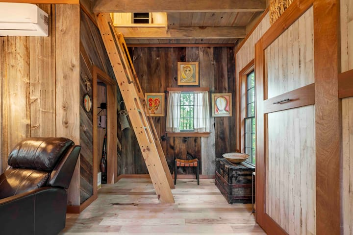The treehouse is adorned with original art from Senegal and South Africa. The ladder leads to an upstairs sleeping loft and balcony. The cabinet reveals a queen-size bed with a comfy memory foam mattress and cotton linens.  Credit: Dickersonarts.com