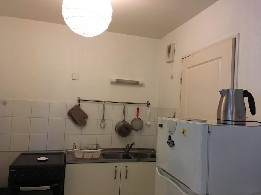 Cuisine tout équipée : plaque de cuisson, lave linge, frigo, congélateur, micro-ondes, four, machine à café, bouilloire.