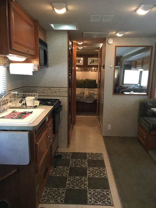 Motorhome features a full kitchen with oven/stove, microwave, and refrigerator/freezer.