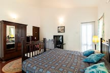 Large bedroom with King size bed over looking the pool