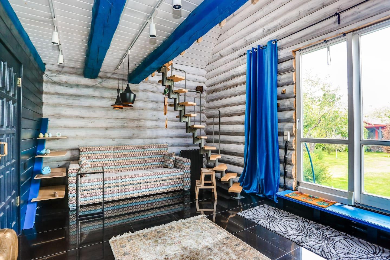 Диван и лестница. В гостиной комнате большая дверь-окно с видом в сад.