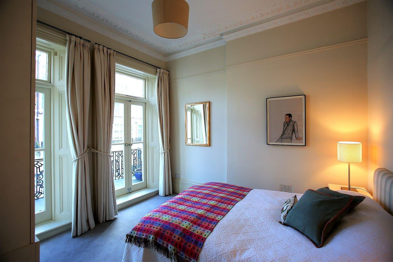Master bedroom with door leading to balcony