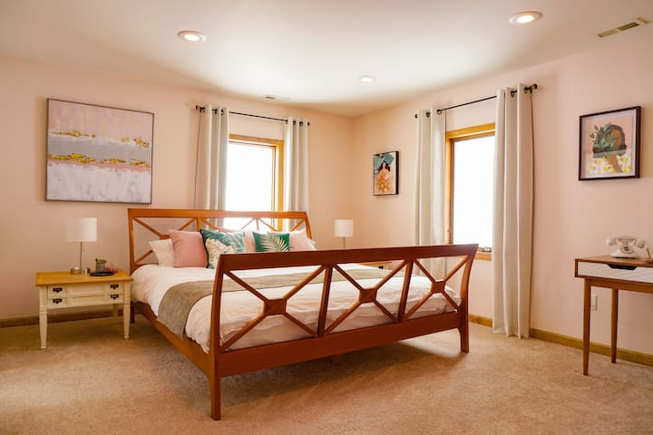 """Our first bedroom is spacious and has a king bed, full-length mirror, desk, en suite bathroom with jacuzzi tub, and 32"""" TV."""