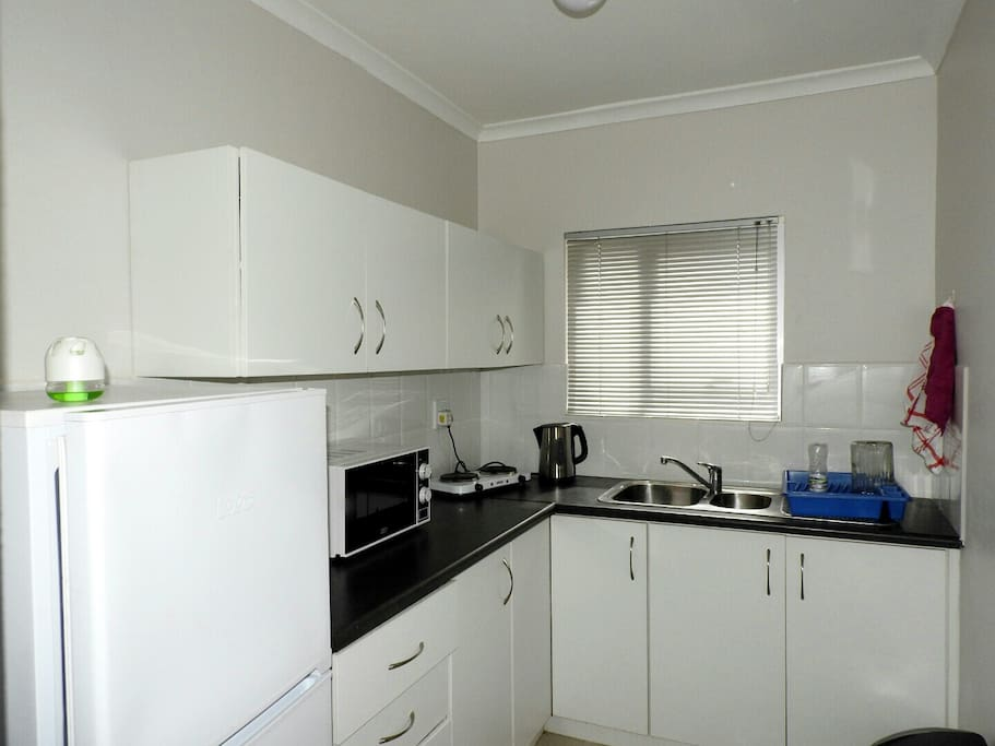Kitchen with appliances. Fridge, Kettle, Microwave, Toaster and small two plates stove.