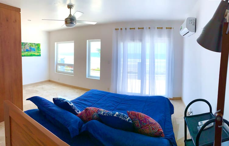 A king size bed faces the beach balcony in the upstairs master bedroom.