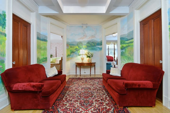 Velvet couches and a mural in the sitting room outside the king Bridal Suite and Railroad Baron suite.