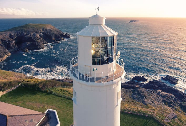 The lighthouse is located on a headland between the sandy beaches of Harlyn and Constantine Bays