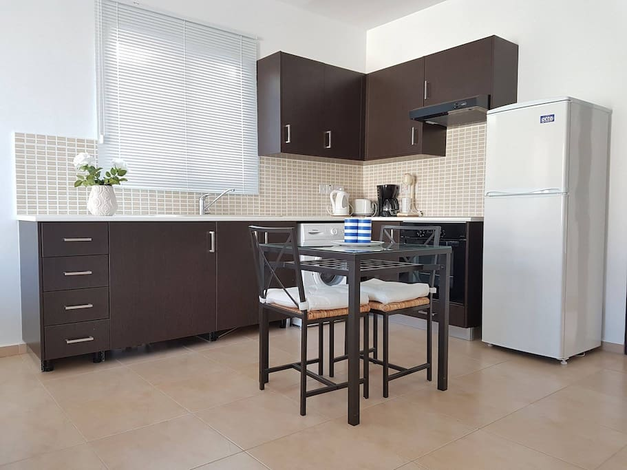 Kitchen with electric stove top, oven, refrigerator, washing machine