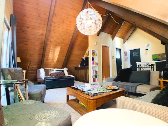 Spacious upstairs family room has three different seating areas and a wet bar, furnished with tons of board games, children's books, and toys.