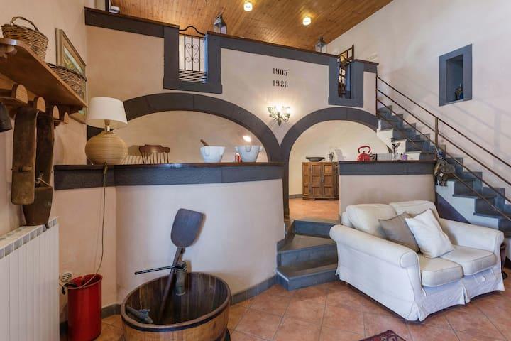 """Spazio living con comodo sofà. Sopra il sofà le nicchie semicircolari del palmento e la scritta con la data di costruzione """"1905""""."""