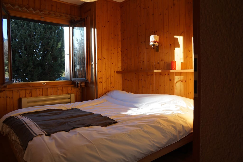Bright double bedroom with fitted wardrobes. Windows open into the garden