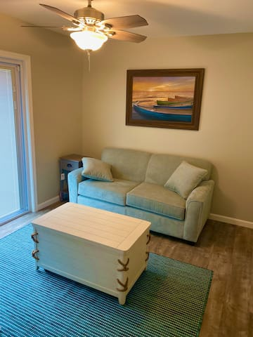 Rear living space. Couch pulls out to full mattress. Private Roku TV. Entry walkway to back porch with optional locking door to make this another bedroom. Stackable washer/dryer in closet.