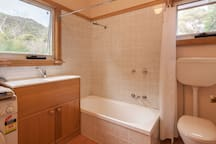 Bathroom with tub, double sink, and washing machine