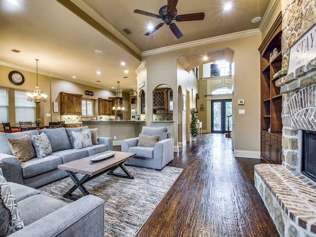 The living room flows into a gourmet kitchen, bar, and breakfast nook