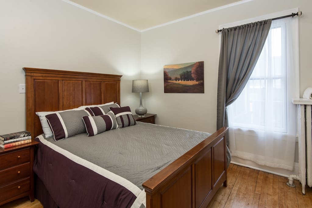Large master bedroom with queen bed and hardwood floors.