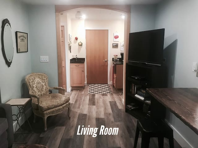 The living room, television and archway to the kitchenette