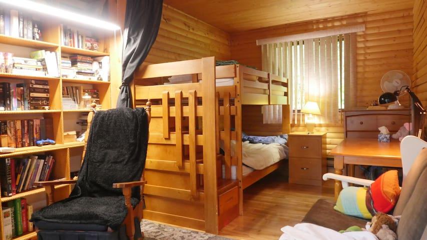 Cette chambre n'a pas de cloison mais j'ai ajouté un rideau pour un minimum d'intimité.  La maison est fait en 8. Alors cette chambre est quand même isolée de la salle de séjour. Ex: les parents peuvent veillés pendant que les enfants dorment.