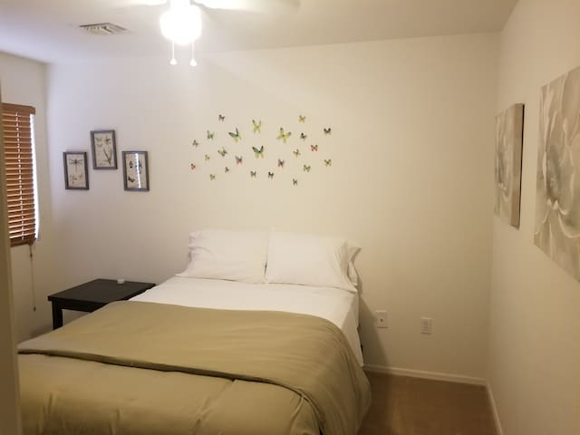 Guest bedroom has a queen size bed. The room also includes a ceiling fan with a low to high air speed.  The relaxing green color is on the duvet and wall decor.  There is a mirror in this room.