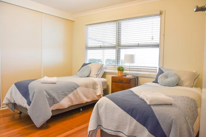 Large bedroom with two single beds. Sliding mirror door with lots of built-in cupboard space.   Close blinds to privatise from back patio area.