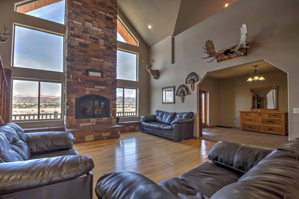 The living area features a large stone fireplace and large windows.