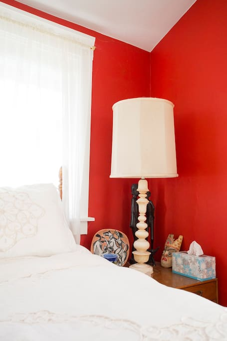Bedside table and lamp on right side of bed.
