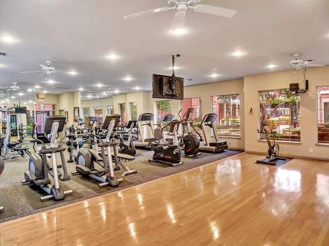 Fitness center includes elliptical, treadmill, bikes, weight stations, cable machines, free weights, yoga matts, and steps.