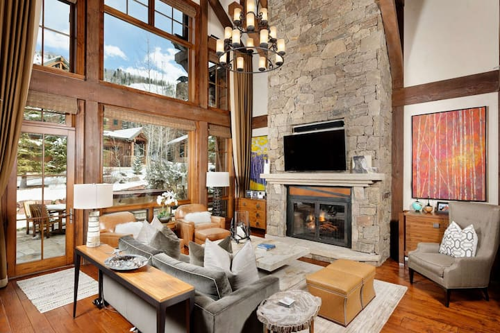 The living area features high vaulted ceilings with wall to wall windows looking up at Aspen Highlands ski area