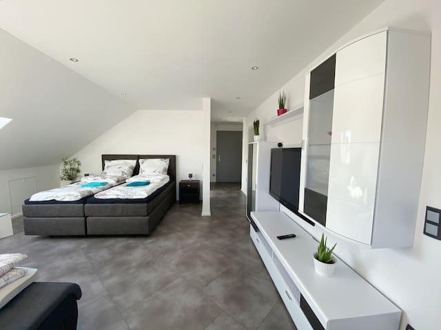 Wohnzimmer mit einem Boxspringbett und einem ausziehbaren Schlafsofa