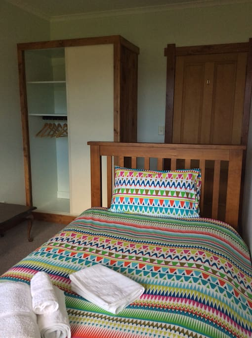 King single bed with wardrobe in the background