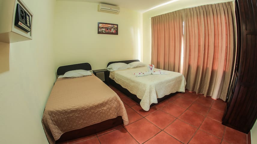 Bedroom with double and single beds with A/C unit
