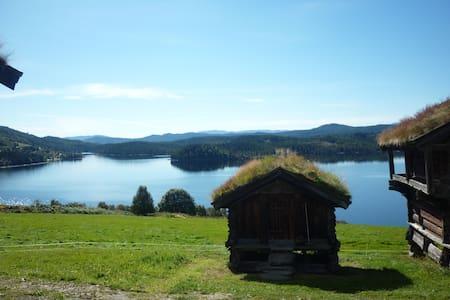 Lita hytte i solfylt gårdstun.