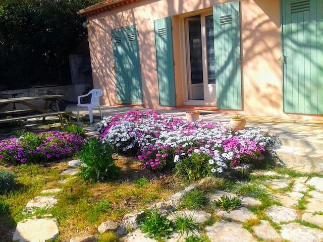 photo de printemps... en été ce sont d'autres fleurs. Jardinet avec table bois barbecue à bois, bûches fournies.