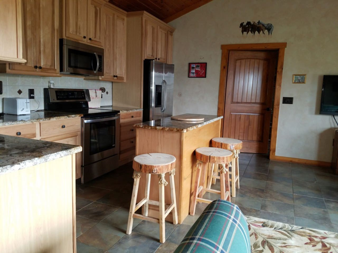 Kitchen with microwave, coffee pot,range, dishwasher and refrigerator. Pots and pans,and dishes.