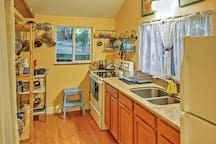 This quaint kitchen comes fully equipped with necessary cooking appliances.