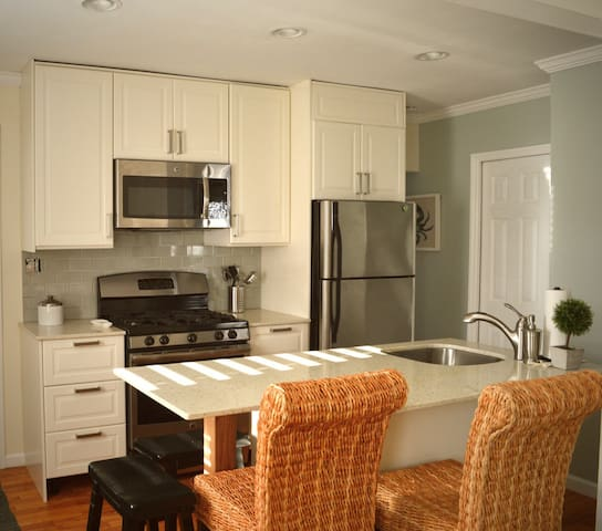 Kitchen with full size gas range, refrigerator, garbage disposal and dishwasher. Pots, pans, flatware, and utensils and glassware are also included.