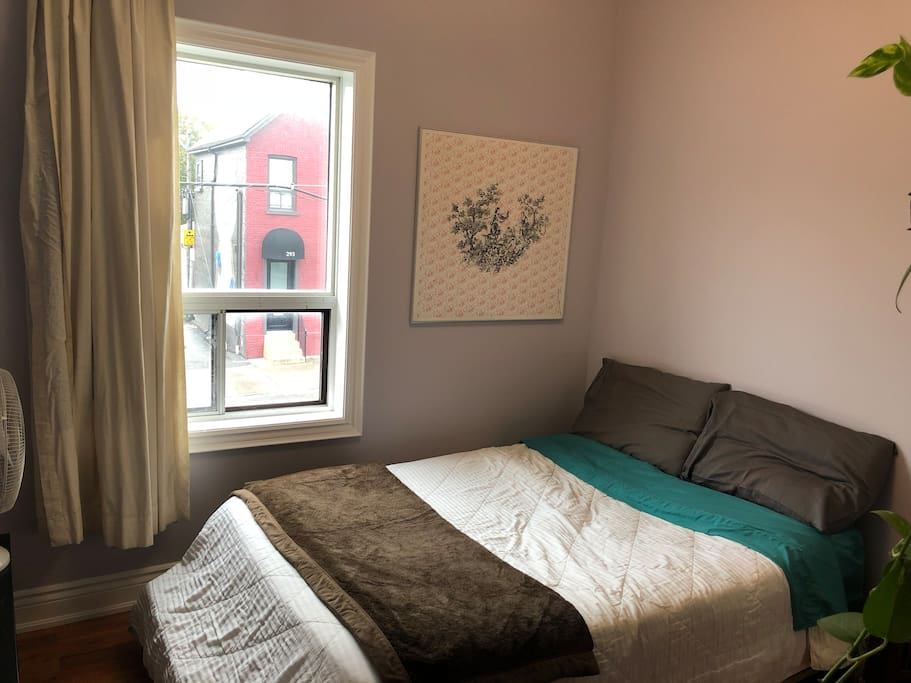 The guest bedroom has a double bed, bright window, closet and dresser.