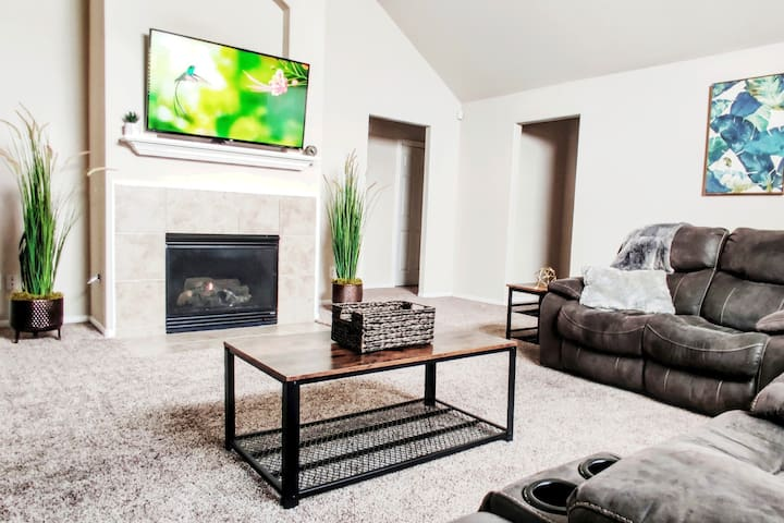 Vaulted Ceilings with Modern touches, Plush sectional, Massive LCD SmartTV, and Fireplace for upscale living.